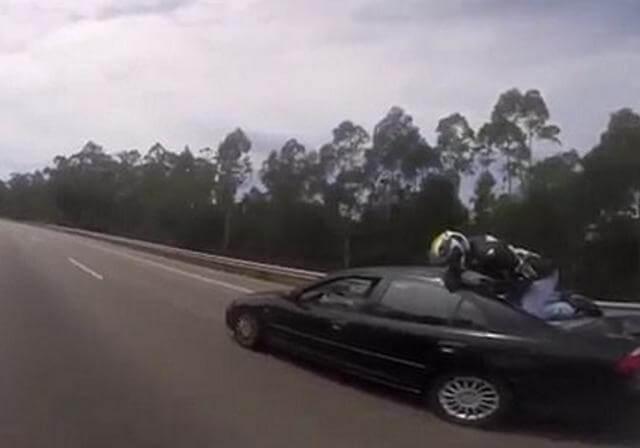 Байкер оказался на крыше автомобиля после столкновения на автотрассе в Португалии. (Видео)