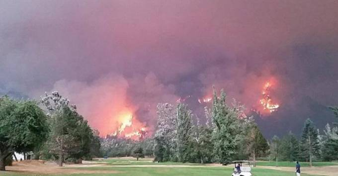 Любители гольфа продолжили игру, не смотря на надвигающуюся огненную стихию, охватившую лес.